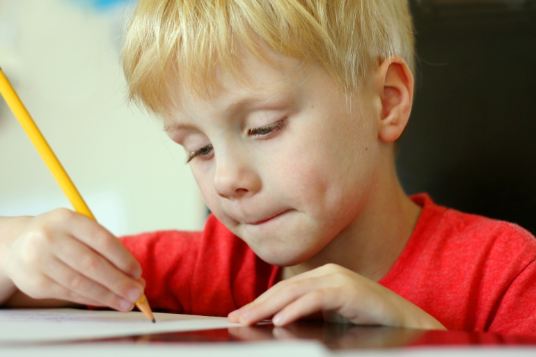Young Child Drawing on Paper with Pencil